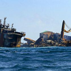 El humo sale del buque portacontenedores MV X-Press Pearl, registrado en Singapur, que transporta cientos de contenedores de productos químicos y plásticos, mientras se remolca desde la costa de Colombo, siguiendo la orden del presidente de Sri Lanka, Gotabaya Rajapaksa, de trasladar el barco a aguas más profundas para evitar un desastre ambiental mayor. | Foto:Ishara S. Kodikara / AFP