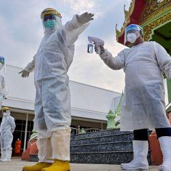 Los voluntarios de rescate de la fundación Siam Nonthaburi se preparan para los funerales de las personas que murieron después de contraer el coronavirus Covid-19 en el templo budista Wat Rat Prakhong Tham en Nonthaburi.   Foto:Lillian Suwanrumpha / AFP