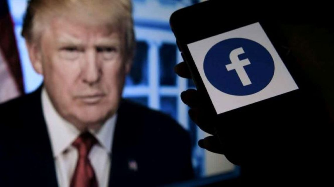 A phone screen displays a Facebook logo with the official portrait of former US President Donald Trump on the background in Arlington, Virginia.