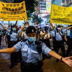 La policía mueve a la gente mientras se reunían en el distrito de Causeway Bay de Hong Kong, después de que la policía cerró el lugar donde la gente de Hong Kong se reúne tradicionalmente anualmente para llorar a las víctimas de la represión de la Plaza de Tiananmen en 1989, las autoridades han prohibido citando la pandemia de coronavirus y prometió acabar con cualquier protesta en el aniversario. | Foto:Isaac Lawrence / AFP