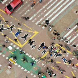 Personas pintan siluetas simulando cadáveres en protesta por miles de ejecuciones extrajudiciales perpetradas por fuerzas militares colombianas, en Bogotá. | Foto:Daniel Munoz / AFP