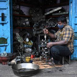 Un trabajador trabaja en un motor en un taller después de que el gobierno alivió un bloqueo impuesto como medida preventiva contra el coronavirus Covid-19, en Chennai. | Foto:Arun Sankar / AFP