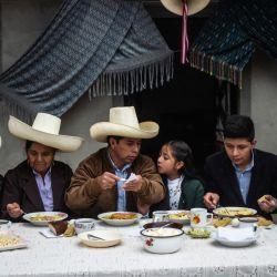 El candidato presidencial de izquierda peruana por el partido Perú Libre, Pedro Castillo acompañado de su familia, participa en un desayuno abierto a la prensa durante la jornada electoral en su casa de Chugur, región de Cajamarca, noreste de Perú. | Foto:Ernesto Benavides / AFP