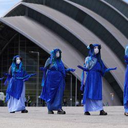 Extinction Rebellion Scotland's Blue Rebels actúan fuera del teatro de conciertos The Armadillo, donde se llevará a cabo la Conferencia de las Naciones Unidas sobre el Cambio Climático Global de 2021 en noviembre, para crear conciencia sobre el aumento del nivel del mar antes de la cumbre del G7.   Foto:Andrew Milligan / PA Wire / DPA