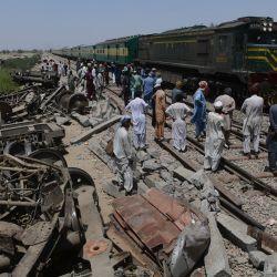 Un tren de pasajeros pasa junto a los restos de un tren en Daharki, un día después de que un tren interurbano lleno se estrellara contra otro expreso que descarriló y mató al menos a 63 personas.   Foto:Asif Hassan / AFP