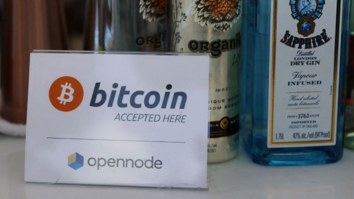 """A """"bitcoin accepted here"""" sign at the bar during the Bitcoin 2021 Convention, a crypto-currency conference held at the Mana Convention Center in Wynwood on June 04, 2021 in Miami, Florida/"""