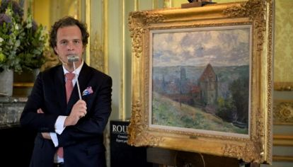 """El rematador francés Aymeric Rouillac posa con """"Dieppe"""", un cuadro de Claude Monet que se quedó sin nuevo dueño."""