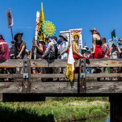 Activistas climáticos y miembros de la comunidad indígena se reúnen en lo alto del puente después de participar en una ceremonia tradicional del agua durante una manifestación y marcha para protestar por la construcción del oleoducto Enbridge Line 3 en Solvay, Minnesota. | Foto:Kerem Yucel / AFP