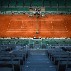 La ucraniana Marta Kostyuk devuelve la pelota a la polaca Iga Swiatek durante el partido de tenis femenino de la cuarta ronda nocturna en la Court Philippe-Chatrier el día 9 del torneo de tenis Roland Garros 2021 del Abierto de Francia en París. | Foto:Christophe Archambault / AFP