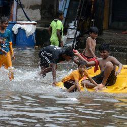 Los niños juegan en una calle anegada después de una fuerte lluvia monzónica en Mumbai. | Foto:Sujit Jaiswal / AFP