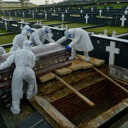 Malasia, Klang: Trabajadores de servicios funerarios con equipo de protección personal se preparan para enterrar el ataúd de una víctima del coronavirus en un cementerio de Klang. | Foto:Kepy / ZUMA Wire / DPA
