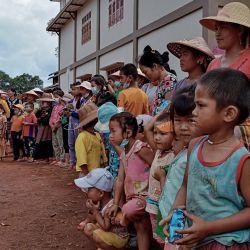 Niños y ancianos desplazados por los recientes combates entre tropas gubernamentales y rebeldes étnicos en su área, esperan la distribución de alimentos de un grupo de voluntarios mientras se refugian en un monasterio en la ciudad de Namlan, en el estado oriental de Shan en Myanmar. | Foto:MNWN / AFP