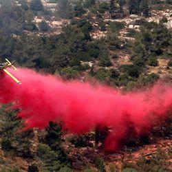 Un avión de extinción de incendios trabaja en la extinción de un incendio forestal en el área de la aldea árabe-israelí de Abu Ghosh, cerca de Jerusalén.   Foto:Ahmad Gharabli / AFP