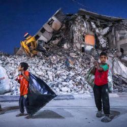 Niños palestinos pasan frente a la destruida torre Al-Shuruq en el barrio al-Rimal de la ciudad de Gaza, que fue blanco de ataques israelíes durante los recientes enfrentamientos entre Hamas e Israel.   Foto:Mohammed Abed / AFP