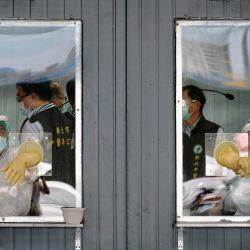 En la imagen se ve al personal médico detrás de sus áreas de trabajo selladas en un área de detección de prueba de hisopo para el coronavirus Covid-19 en la ciudad de Nueva Taipei.   Foto:Sam Yeh / AFP
