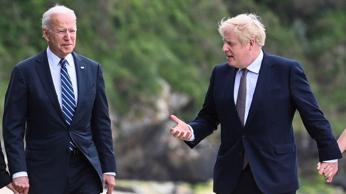 Britain's Prime Minister Boris Johnson speaks with US President Joe Biden while they walk at Carbis Bay, Cornwall on June 10, 2021, ahead of the three-day G7 summit being held from 11-13 June.