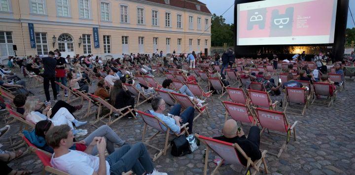 Los visitantes esperan la proyección de la serie de televisión 'Ich und die Anderen' (Yo y los demás) frente al palacio de Charlottenburg como parte del festival de cine 'Berlinale Summer Special' en Berlín.