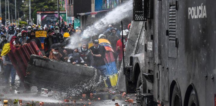 Agentes de la policía rocían con un cañón de agua a los manifestantes durante una protesta contra el gobierno del presidente colombiano Iván Duque en Bogotá.