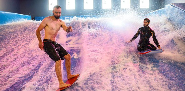Hombres surfean durante la inauguración de Wave In, el primer centro de surf indoor de París, con ola estática.