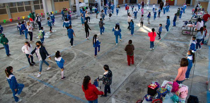 Los niños hacen ejercicio antes de ingresar a las aulas durante la reanudación de las clases presenciales en la Ciudad de México, luego de que las actividades educativas fueran suspendidas debido a la pandemia del coronavirus COVID-19 durante más de un año. - La asistencia no es obligatoria ni para estudiantes ni para profesores.