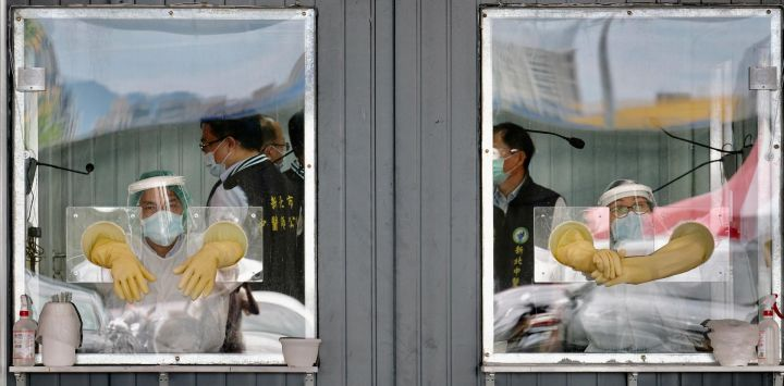 En la imagen se ve al personal médico detrás de sus áreas de trabajo selladas en un área de detección de prueba de hisopo para el coronavirus Covid-19 en la ciudad de Nueva Taipei.