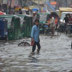 Los viajeros atraviesan una calle anegada después de un fuerte aguacero en Dhaka. | Foto:Munir Uz Zaman / AFP