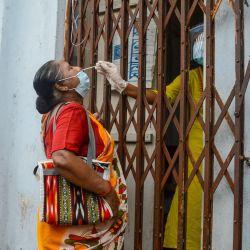 Un trabajador de la salud recolecta una muestra de hisopo para la prueba de Coronavirus (Covid-19) de una dama frente a un centro de salud en Calcuta. | Foto:Debarchan Chatterjee / ZUMA Wire / DPA