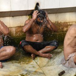 Las personas se bañan en un lugar de baño común en medio de un aumento de las temperaturas durante un caluroso día de verano en Amritsar. | Foto:Narinder Nanu / AFP