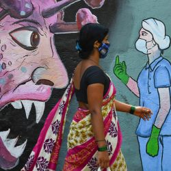 Un peatón pasa junto a un mural que muestra a un personal médico de primera línea deteniendo el coronavirus Covid-19, en Navi Mumbai. | Foto:Indranil Mukherjee / AFP