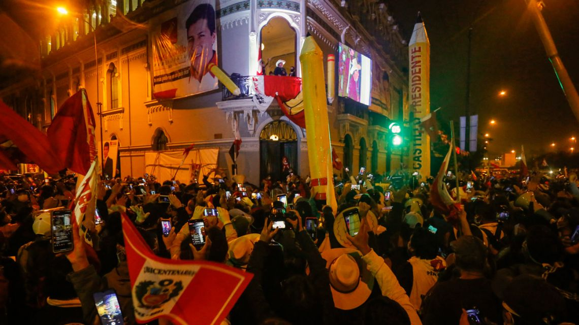 Peru's left-wing presidential candidate Pedro Castillo of the Peru Libre party, gestures as he speaks to his supporters from the balcony of his party headquarters in Lima on June 10, 2021.