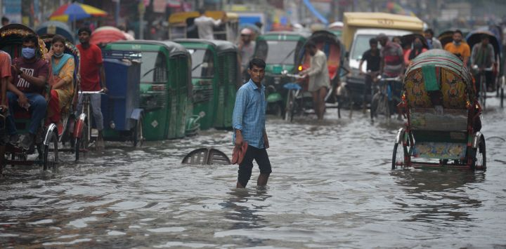 Los viajeros atraviesan una calle anegada después de un fuerte aguacero en Dhaka.