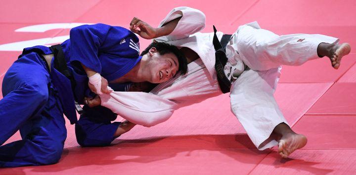El estadounidense Colton Brown (blanco) lucha contra el surcoreano Juyeop Han (azul) en la categoría masculina de -90 kg durante el quinto día del Campeonato Mundial de Judo de 2021 en la Arena 'Papp Laszlo' de Budapest Hungría.