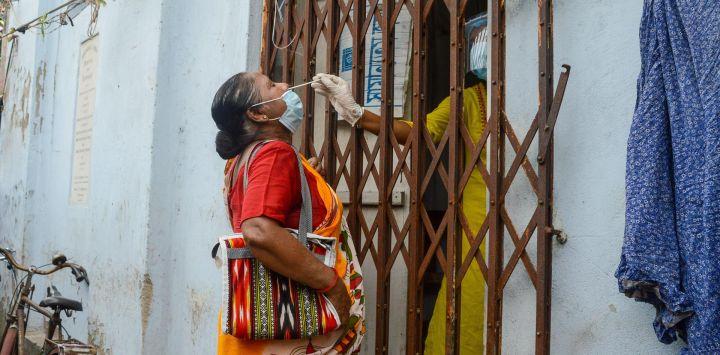 Un trabajador de la salud recolecta una muestra de hisopo para la prueba de Coronavirus (Covid-19) de una dama frente a un centro de salud en Calcuta.