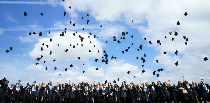 Los alumnos lanzan sus birretes al aire después de una ceremonia de graduación en su último día de clases en BBG Academy en Bradford.