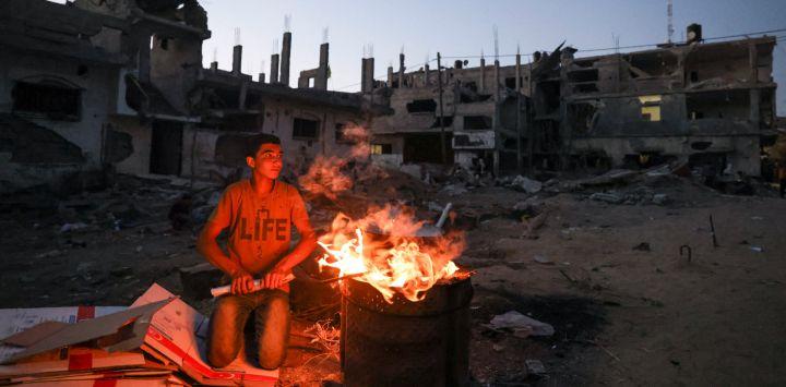 Un joven palestino se prepara para cocinar maíz cerca de edificios destruidos durante el conflicto de mayo de 2021 entre Hamas e Israel, en Beit Hanun, en el norte de la Franja de Gaza.