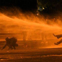 Un manifestante cae al ser alcanzado por un cañón de agua durante los enfrentamientos con la policía antidisturbios en medio de las protestas en curso contra el gobierno del presidente colombiano Iván Duque en Bogotá.   Foto:Juan Barreto / AFP