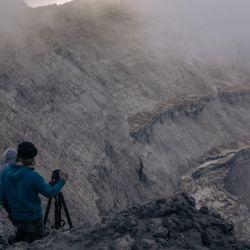 Christopher Horsley (derecha), asistente técnico de vulcanólogos congoleños, toma fotografías del cráter del volcán Nyiragongo, al norte de Goma, la capital provincial de Kivu del Norte.   Foto:Alexis Huguet / AFP