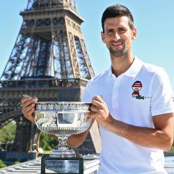 El serbio Novak Djokovic posa con el trofeo frente a la torre Eiffel, en París, durante un photocall un día después de ganar el torneo de tenis Roland Garros 2021.   Foto:Christophe Archambault / POOL / AFP