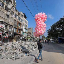 Un vendedor ambulante palestino camina con bolsas de algodón de azúcar junto a los escombros de un edificio destruido durante el conflicto de mayo de 2021 entre Hamás e Israel en el barrio de al-Rimal de la ciudad de Gaza.   Foto:Mohammed Abed / AFP