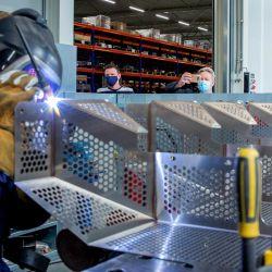 Un empleado de la empresa Veluw Metal Creations trabaja en una pieza metálica junto a la Reina Máxima de Holanda en Nieuwkuijk. - La visita de la Reina Máxima se centró en la innovación, la sostenibilidad, la movilidad laboral y las consecuencias de la crisis de Covid-19 para el sector del metal. | Foto:Wesley de Wit / ANP / AFP