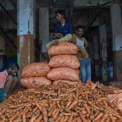 Los trabajadores clasifican las verduras en un mercado mayorista en Navi Mumbai. | Foto:Punit Paranjpe / AFP