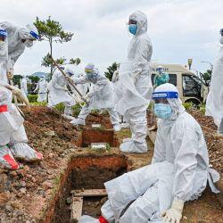 Voluntarios con trajes de protección descansan después de enterrar el cuerpo de una víctima del coronavirus Covid-19 en el cementerio musulmán Raudhatul Sakinah en Kuala Lumpur. | Foto:Mohd Rasfan / AFP