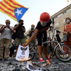 Manifestantes antimonárquicos queman fotos del rey español durante una protesta contra la visita del rey Felipe VI de España a Cataluña, en Barcelona. | Foto:Josep Lago / AFP