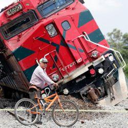 Un hombre con una bicicleta pasa junto a un tren que se descarriló en la comunidad de San Isidro Mazatepec en Tala, Estado de Jalisco, México. | Foto:Ulises Ruiz / AFP