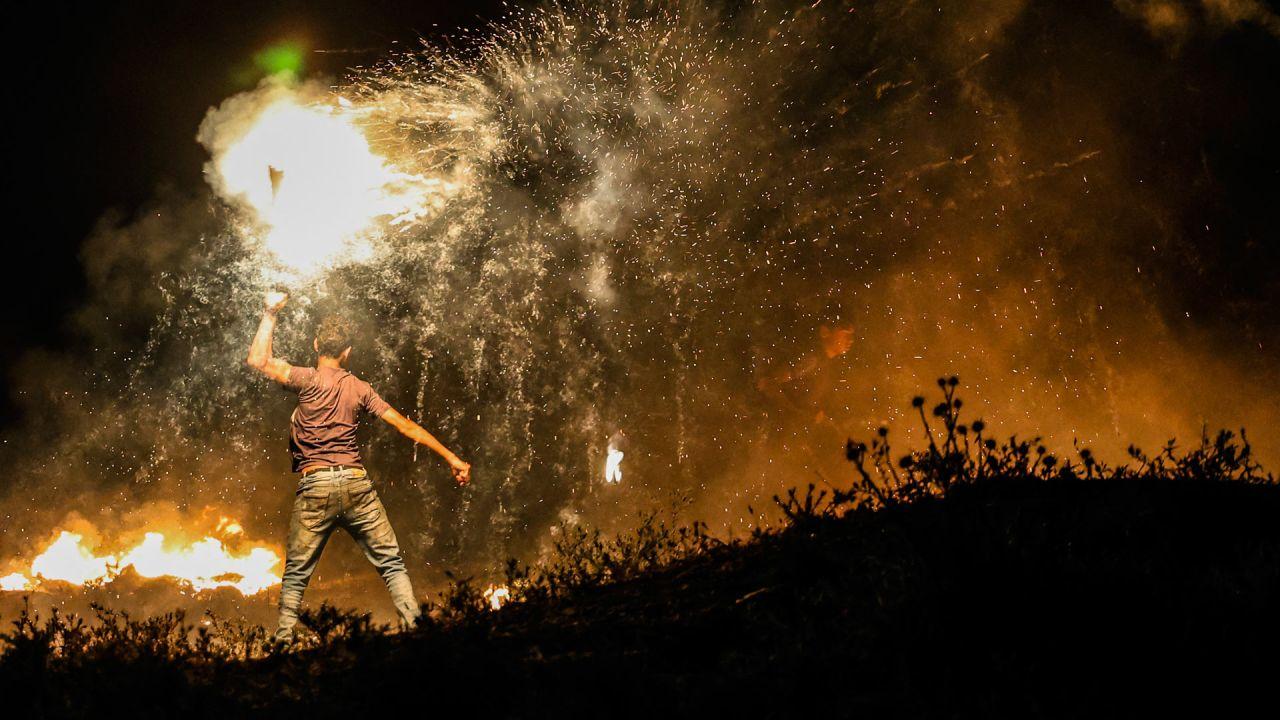 Un manifestante palestino lanza un proyectil en llamas hacia las fuerzas israelíes durante una manifestación al este de la ciudad de Gaza, junto a la frontera con Israel, para protestar contra la ultranacionalista Marcha de las Banderas israelí en la Ciudad Vieja de Jerusalén, que celebra el aniversario de la ocupación israelí del sector oriental de Jerusalén en 1967. | Foto:Mahmud Hams / AFP