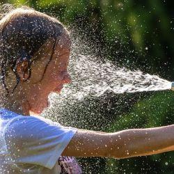 Mattis, de nueve años, se refresca con agua fría de la manguera del jardín durante una calurosa ola de verano. | Foto:Jens Büttner / DPA