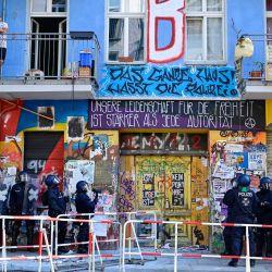 Unas personas se asoman a un balcón mientras la policía se prepara para entrar en un edificio de la calle Rigaer Strasse, en el distrito berlinés de Friedrichshain, donde estaba prevista una inspección de protección contra incendios por parte de los bomberos y a la que se oponían algunos residentes que ocupaban el edificio. | Foto:John Macdougall / AFP