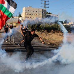 Un manifestante palestino devuelve un bote de gas lacrimógeno disparado por las fuerzas israelíes durante una manifestación cerca del asentamiento judío de Beit El, cerca de Ramallah, en la Cisjordania ocupada, en protesta por la Marcha de las Banderas ultranacionalista israelí en la Ciudad Vieja de Jerusalén que celebra el aniversario de la ocupación israelí del sector oriental de Jerusalén en 1967. | Foto:Abbas Momani / AFP