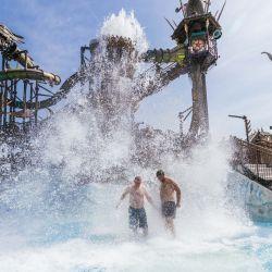 Dos hombres permanecen bajo una cascada artificial en el recinto de la piscina de atracciones Rulantica en medio de una ola de alta temperatura. | Foto:Philipp von Ditfurth / DPA