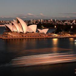 Esta imagen de obturación lenta muestra los tonos del atardecer cayendo sobre las velas del emblemático edificio de la Ópera mientras un ferry se abre paso por el puerto de Sídney. | Foto:Saeed Khan / AFP